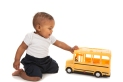 Little African American Baby Boy Pushing Toy School Bus on White