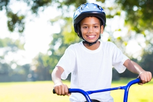 happy young boy riding a bike outdoors